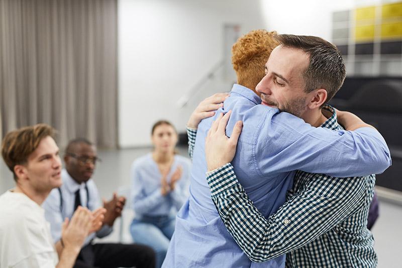two men hugging in rehab