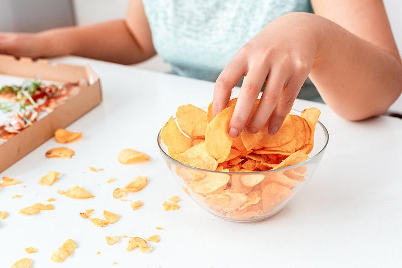a woman bingeing on snacks