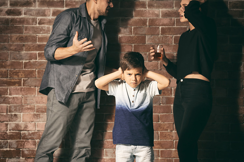 a young boy covering his ears as his parents argue